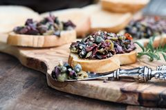 Delicious Tapenade on Toasted Bread. Homemade mixed Olive Tapenade made with garlic, capers, olive oil, Kalamata, black and green olives spread over toasted stock image