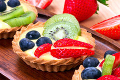 Delicious tart dessert. Delicious custard tart with blueberries, kiwi and strawberries Royalty Free Stock Photography