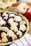 Delicious tart filled with peaches and blueberries Royalty Free Stock Photography