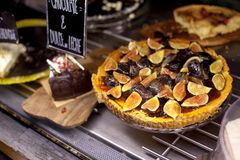 Delicious tart with fresh figs on display showcase. Modern bakery with different kinds of cakes and buns. Market, cafe stock images