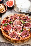 Delicious  tart with fresh  figs and goat cheese on rustic wooden Royalty Free Stock Image