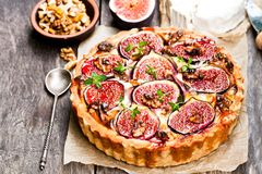 Delicious  tart  with fresh figs and goat cheese on rustic wooden Stock Images