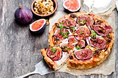 Delicious  tart with fresh figs and goat cheese on rustic wooden. Delicious  tart with fresh  figs and goat cheese on rustic wooden table Stock Photography