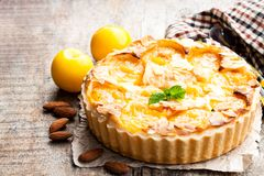 Delicious  tart with yellow plum and almonds on wooden table Stock Images