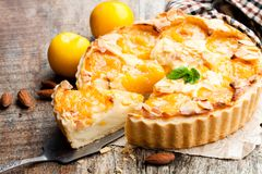 Delicious  tart with yellow plum  and almonds on wooden table Royalty Free Stock Photography