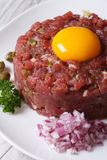 Delicious tartare of beef closeup on a white plate Stock Photos