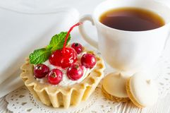 Delicious tartlet with fresh berries and cream cheese, a сup of tea and small cookies royalty free stock image
