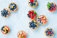 Delicious tartlets or cake with mixed berry on blue background from above. Summer pastry desserts. Royalty Free Stock Images
