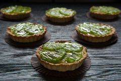 Delicious tartlets filled with cream and topped with kiwi slices. Sweet tarlets with fruits Stock Photo