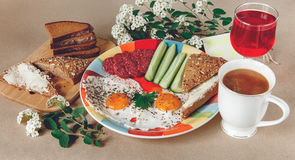 Delicious Tasty Breakfast from Eggs,Bread with Butter,Sausage on the Colorfull Plate.Coffee,Red Juice  with White Flowers. Stock Image