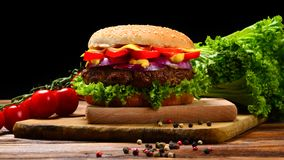 Delicious tasty burger with beef, tomatoes, salad and sauce on wooden table and black background. royalty free stock photos