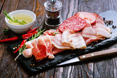Delicious and tasty meat dishes. On the board Stock Photos