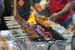 Chicken satay street market scene. Delicious tasty skewers of chicken cook over hot coals in Singapore`s Satay Street food market royalty free stock image