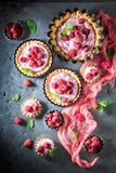 Delicious and tasty tarts with raspberries and mascarpone. On old table stock photo