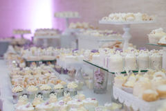 Delicious & tasty white decorated cupcakes at wedding reception Stock Photo