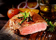 Delicious tender beef steak on a chopping board Royalty Free Stock Photo