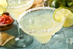 Tequila and Lime Margaritas. Delicious tequila and lime margaritas on an outdoor table with tortilla chips and pico de gallo stock image
