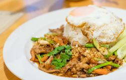Delicious Thai food garlic and pepper with pork and Fried egg wi. Th jasmin rice closeup with carrot cucumber Spring onion and coriander leaves on top in white stock photo