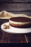 Delicious three-layer chocolate cake stands on a circular base. Lying next to rushy sugar and tongs on a wooden table and dark background. place for text. food Stock Photos
