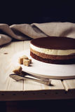 Delicious three-layer chocolate cake stands on a circular base. Lying next to rushy sugar and tongs on a wooden table and dark background. place for text. food Royalty Free Stock Image