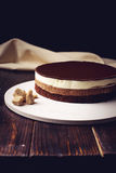 Delicious three-layer chocolate cake stands on a circular base. Lying next to rushy sugar and tongs on a wooden table and dark background. place for text. food Royalty Free Stock Images