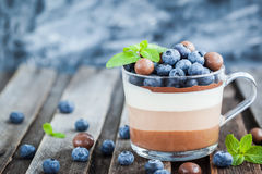 Delicious three layered chocolate mousse dessert, devorated wit. H fresh blueberry, mint and candies, served in glass cup stock photo