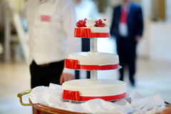 Delicious three stories white wedding cake. With red bows Stock Photos
