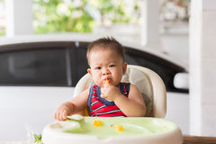 Delicious time of baby. The baby learns to eat by himself. he can use spoon well. so he is very happy (focus at his face Stock Photography