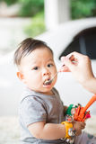 Delicious time of baby. The baby learns to eat by himself. he can use spoon well. so he is very happy but his parent still feed him(focus at his face Royalty Free Stock Photography