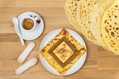 Delicious tiramisu crepe filled with mascarpone, coffee and chocolate powder. French crepe with italian tiramisu from top. Delicious tiramisu crepe filled with royalty free stock photos