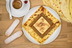 Delicious tiramisu crepe filled with mascarpone, coffee and chocolate powder. French crepe with italian tiramisu close up. Delicious tiramisu crepe filled with stock image