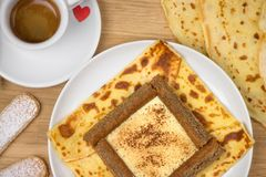 Delicious tiramisu crepes filled with mascarpone, coffee and chocolate powder. French crepe with italian tiramisu. Delicious tiramisu crepe filled with stock photos