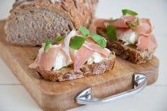 Delicious toast. Small piece of bread with pesto, mozarella, ham and basil Stock Photos