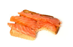 Delicious toast with smoked salmon #2. Bitten piece of toast casts a small shadow royalty free stock photography
