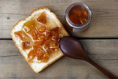 Delicious toasts with sweet jams and spoon on wooden background, top view, copy space royalty free stock image