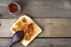 Delicious toasts with sweet jams and spoon on wooden background, top view, copy space stock image