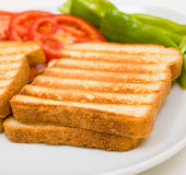 Delicious toasts with tomatos and peppers. Delicious toasts with sliced tomatoes and green peppers. Close-up studio shot Royalty Free Stock Photos
