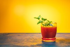 Delicious tomato bloody mary cocktail on dark blue concrete table. With spot light. Yellow background royalty free stock image