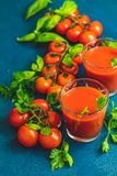 Delicious tomato bloody mary cocktail on dark blue concrete table. Tomato juice, red cocktail with tomato juice between tomatoes, fresh basil and ice. Delicious royalty free stock image