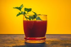 Delicious tomato bloody mary cocktail with spot light. Delicious tomato bloody mary cocktail on dark blue concrete table with spot light. Yellow background royalty free stock photo