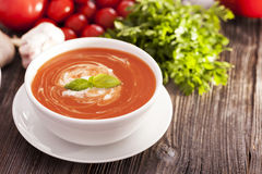 Delicious tomato soup with aromatic spices on a wooden table. Stock Photos