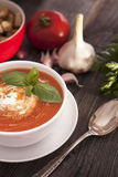 Delicious tomato soup with aromatic spices on a wooden table. Stock Photography