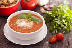 Delicious tomato soup with aromatic spices on a wooden table. Royalty Free Stock Photo