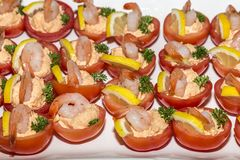 Delicious tomatoes stuffed with salad and decorated with a shrimp, parsley and lemon stock images