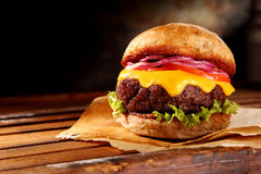 Delicious traditional cheeseburger. With melted cheese and fresh salad trimmings on a juicy thick beef patty, close up low angle view with copy space stock photos