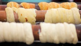 Delicious trdelnik browning on wooden sticks at high temperature, Czech cuisine. Stock footage stock footage