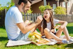 Caring father feeding grapes to her little daughter. Delicious treat. Caring young father sitting on the grass and feeding grapes to his beloved little daughter Stock Image