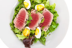 Delicious tuna steak with fresh green salad. On white plate, top view on white background. Culinary seafood eating Stock Photo