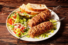 Delicious Turkish adana skewers or kebabs. Made from minced spicy young lamb roasted over oak served on a plate with fresh salad Royalty Free Stock Photography