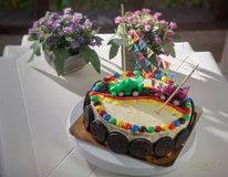 Delicious vanilla cake for children birthday party. Decorated with toys sport cars and chocolate cookies stock photography